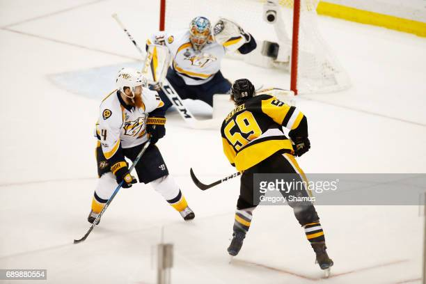 Jake Guentzel of the Pittsburgh Penguins shoots a goal as Pekka Rinne of the Nashville Predators defends during the third period in Game One of the...