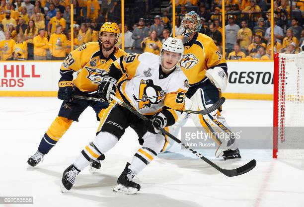 Jake Guentzel of the Pittsburgh Penguins skates against Roman Josi in front of goalie Pekka Rinne of the Nashville Predators during Game Three of the...