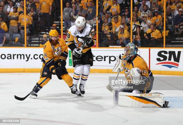 Jake Guentzel of the Pittsburgh Penguins skates in the slot area for the screen as goaltender Pekka Rinne of the Nashville Predators gets in position...