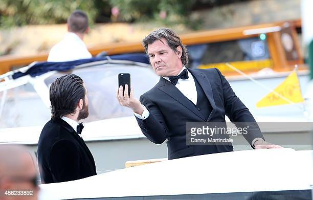 Jake Gyllenhaal and Josh Brolin take photo's of each other as they arrive by water taxi to the 'Everest' Premiere on day 1 of the 72nd Venice Film...