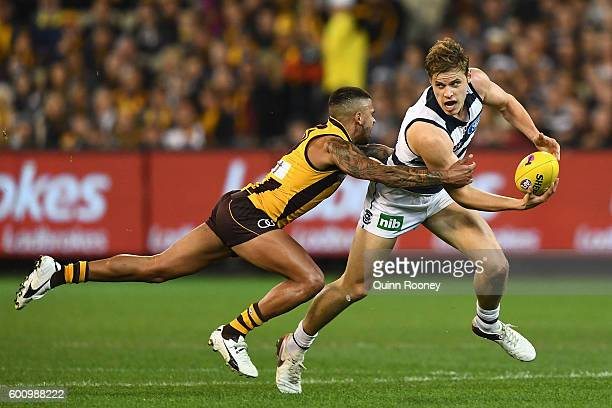 Jake Kolodjashnij of the Cats handballs whilst being tackled Bradley Hill of the Hawks during the 2nd AFL Qualifying Final match between the Geelong...