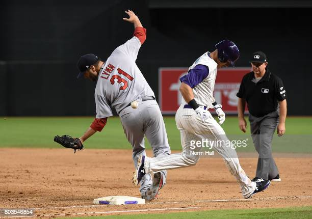Jake Lamb of the Arizona Diamondbacks beats out the throw to first base as the ball gets away from Lance Lynn of the St Louis Cardinals during the...