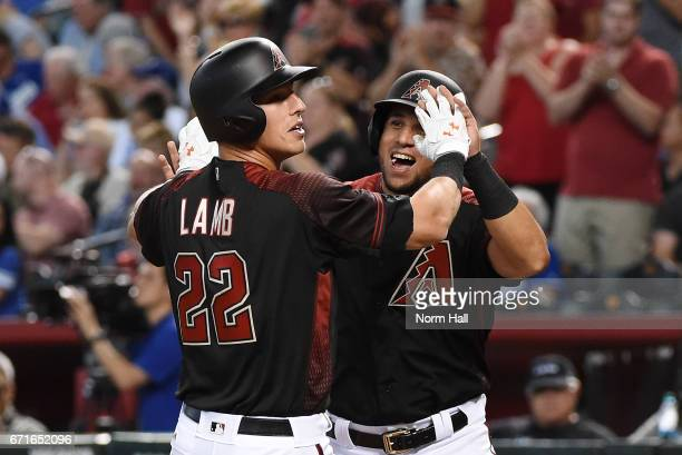 Jake Lamb of the Arizona Diamondbacks celebrates with teammate David Peralta after hitting a first inning home run off of Kenta Maeda of the Los...