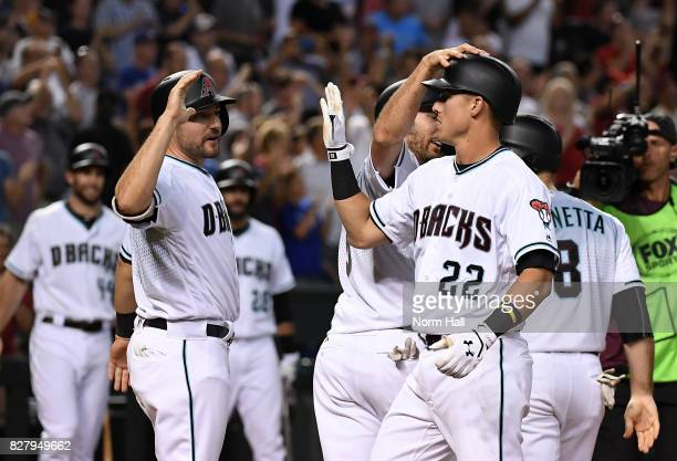 Jake Lamb of the Arizona Diamondbacks celebrates with teammates AJ Pollock and Adam Rosales after hitting a grand slam home run during the seventh...