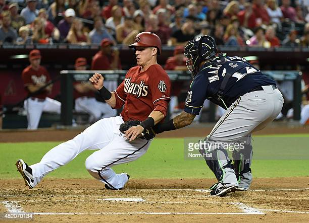 Jake Lamb of the Arizona Diamondbacks is tagged out at home plate by Martin Maldonado of the Milwaukee Brewers during the second inning at Chase...
