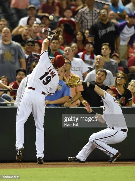 Jake Lamb of the Arizona Diamondbacks makes a catch in foul territory just in front of teammate Cliff Pennington during the sixth against the...