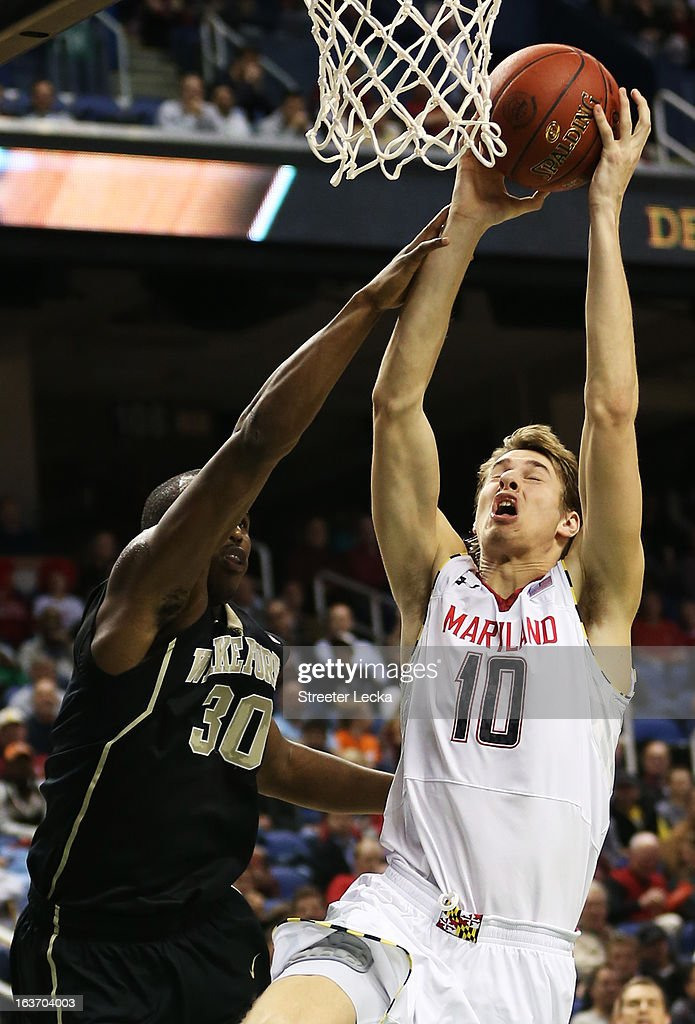 Jake Layman #10 of the Maryland Terrapins dunks over Travis McKie #30 of the Wake Forest Demon Deacons in the second half of their game during the first round of the Men's ACC Basketball Tournament at Greensboro Coliseum on March 14, 2013 in Greensboro, North Carolina.