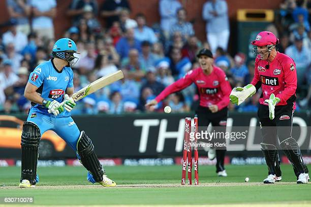 Jake Lehmann of the Adelaide Strikers looks back after getting bowled out as Brad Haddin of the Sydney Sixers celebrates during the Big Bash League...