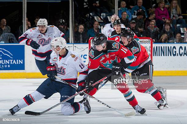 Jake Leschyshyn of the Regina Pats is checked by Kole Lind of the Kelowna Rockets during first period on November 26 2016 at Prospera Place in...