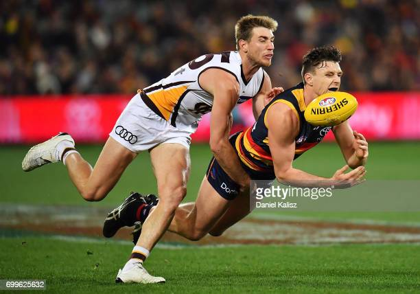 Jake Lever of the Crows handballs as he is tackled by Ryan Schoenmakers of the Hawks during the round 14 AFL match between the Adelaide Crows and the...