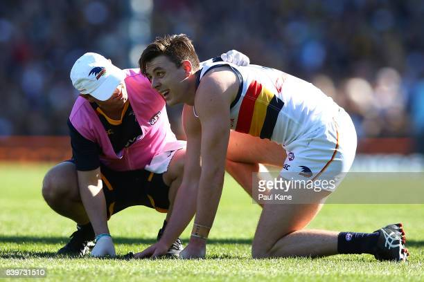 Jake Lever of the Crows is checked by a trainer after a head clash during the round 23 AFL match between the West Coast Eagles and the Adelaide Crows...