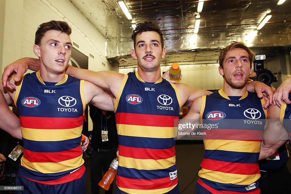 Jake Lever, Taylor Walker and Richard Douglas of the Crows celebrates in the rooms after the round six AFL match between the Adelaide Crows and the Fremantle Dockers at Adelaide Oval on April 30, 2016 in Adelaide, Australia.