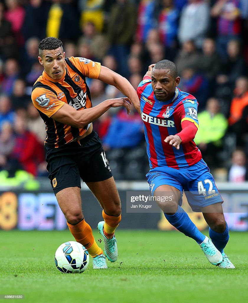 Jake Livermore of Hull City battles for the ball with Jason Puncheon of Crystal Palace during the Barclays Premier League match between Hull City and Crystal Palace at KC Stadium on October 4, 2014 in Hull, England.