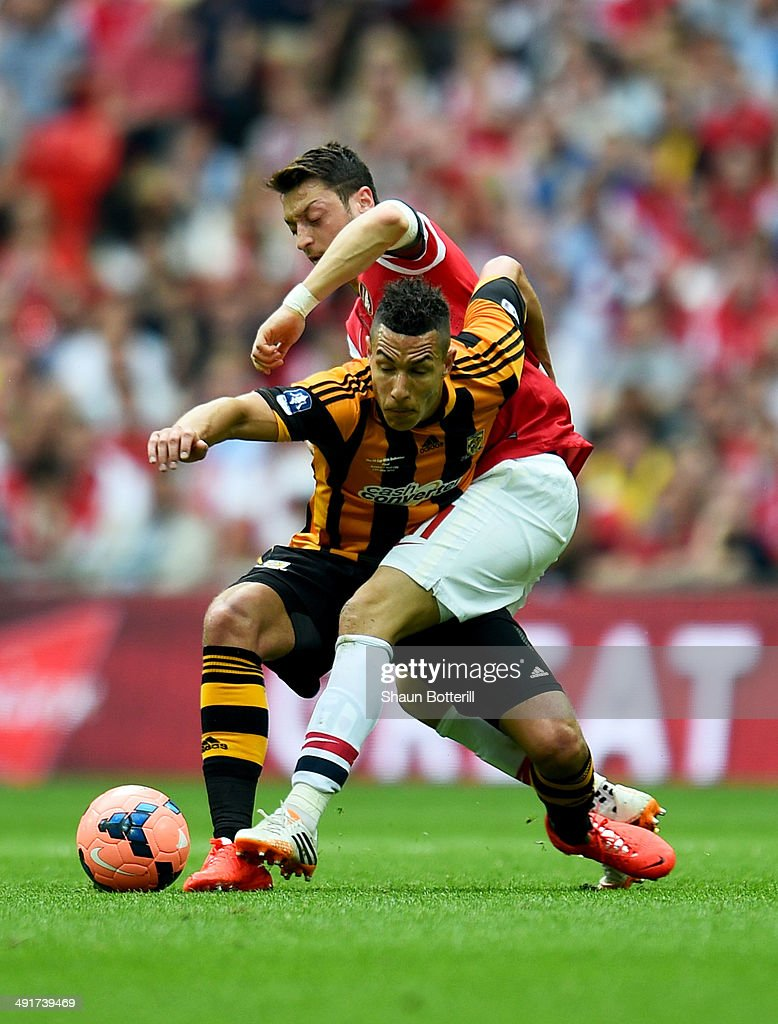 Jake Livermore of Hull City battles with Mesut Oezil of Arsenal during the FA Cup with Budweiser Final match between Arsenal and Hull City at Wembley Stadium on May 17, 2014 in London, England.