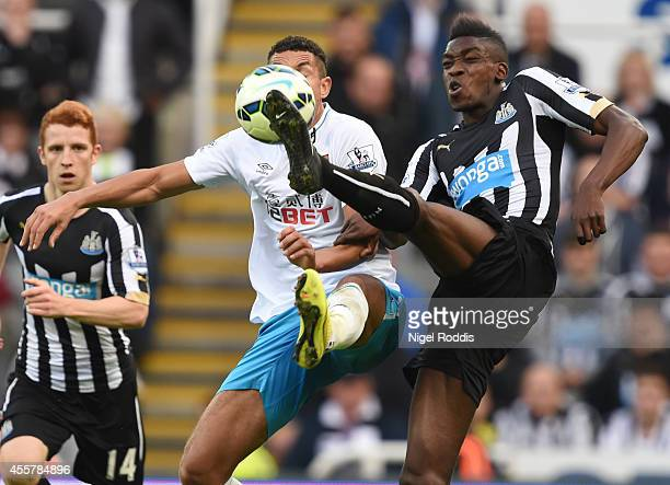 Jake Livermore of Hull City challenged by Sammy Ameobi of Newcastle United during Premier League Football match between Newcastle United and Hull...