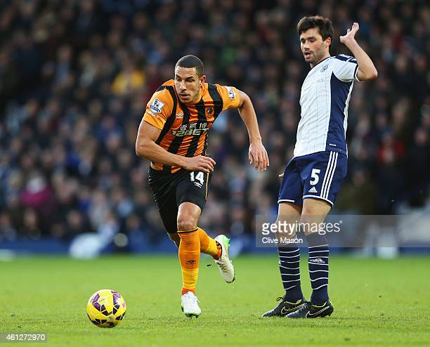 Jake Livermore of Hull City evades Claudio Yacob of West Bromwich Albion during the Barclays Premier League match between West Bromwich Albion and...