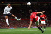 Jake Livermore of Tottenham Hotspur attempts to block the kick by Jonny Evans of Manchester United during the Barclays Premier League match between...