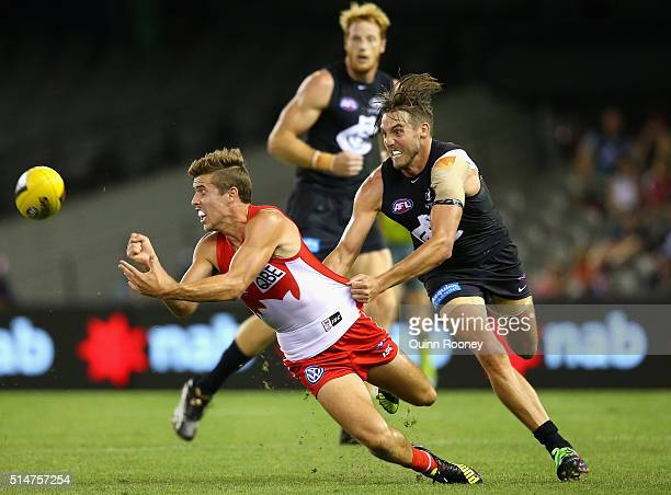 Jake Lloyd of the Swans handballs whilst being tackled by Dale Thomas of the Blues during the NAB Challenge AFL match between the Carlton Blues and...
