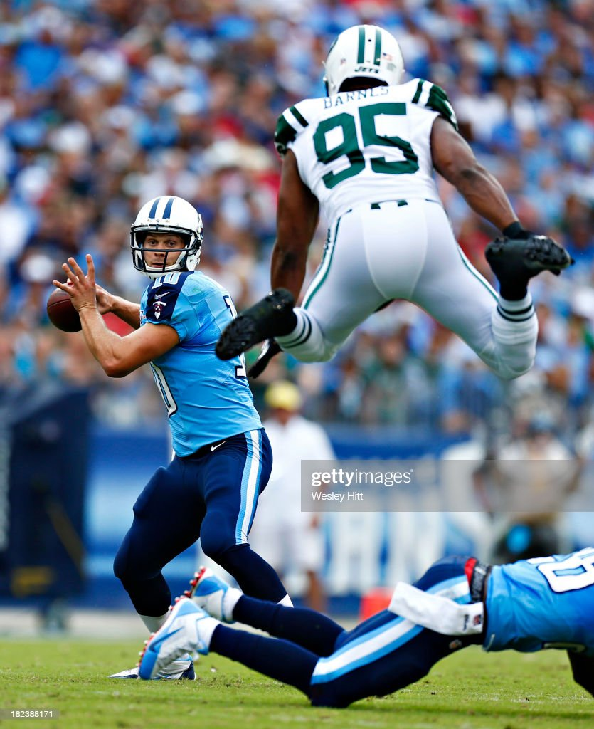 <a gi-track='captionPersonalityLinkClicked' href=/galleries/search?phrase=Jake+Locker&family=editorial&specificpeople=4450185 ng-click='$event.stopPropagation()'>Jake Locker</a> #10 of the Tennessee Titans looks to throw a pass while under pressure from <a gi-track='captionPersonalityLinkClicked' href=/galleries/search?phrase=Antwan+Barnes&family=editorial&specificpeople=3959274 ng-click='$event.stopPropagation()'>Antwan Barnes</a> #95 of the New York Jets at LP Field on September 29, 2013 in Nashville, Tennessee.