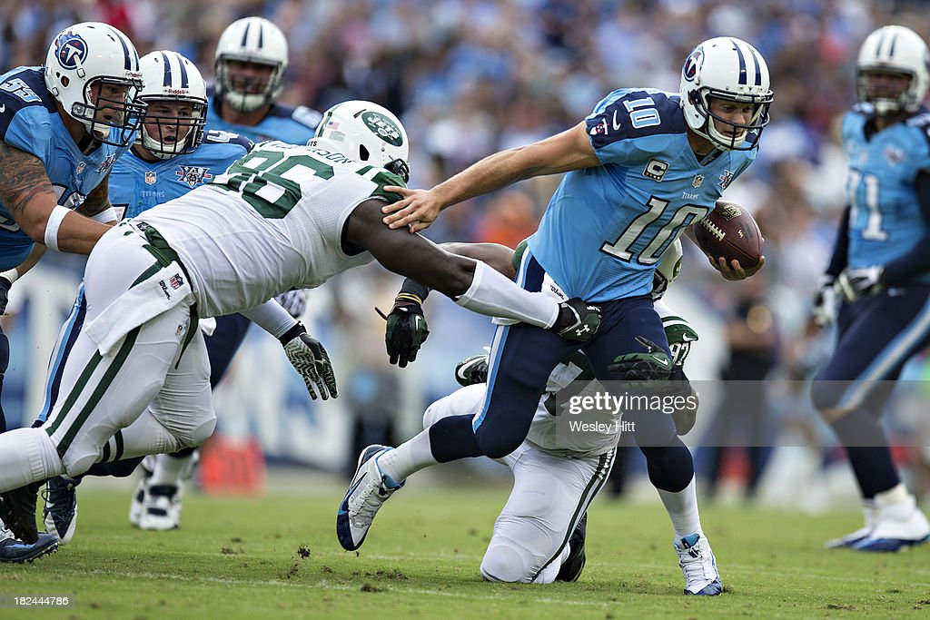 <a gi-track='captionPersonalityLinkClicked' href=/galleries/search?phrase=Jake+Locker&family=editorial&specificpeople=4450185 ng-click='$event.stopPropagation()'>Jake Locker</a> #10 of the Tennessee Titans runs the ball and is hit by <a gi-track='captionPersonalityLinkClicked' href=/galleries/search?phrase=Muhammad+Wilkerson&family=editorial&specificpeople=7542316 ng-click='$event.stopPropagation()'>Muhammad Wilkerson</a> #96 of the New York Jets at LP Field on September 29, 2013 in Nashville, Tennessee. The Titans defeated the Jets 38-13.