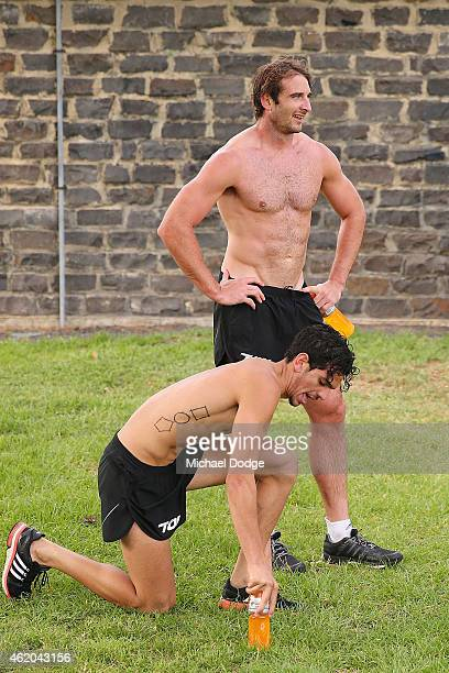 Jake Long and Jobe Watson rest after an Essendon Bombers AFL mini triathlon training session at Williamstown Beach on January 24 2015 in Melbourne...