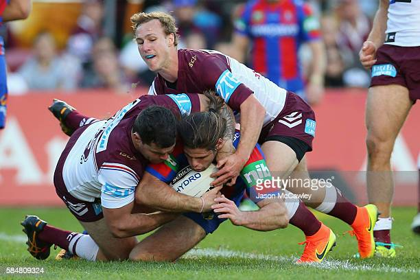 Jake Mamo of the Knights is tackled by Josh Starling and Daly CherryEvans of the Sea Eagles during the round 21 NRL match between the Manly Sea...