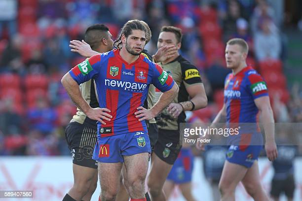 Jake Mamo of the Knights looks dejected as the Panthers celebrate a try during the round 23 NRL match between the Newcastle Knights and the Penrith...