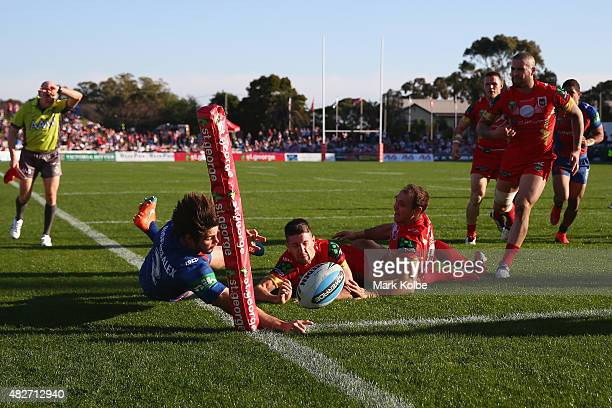 Jake Mamo of the Knights loses the ball as he stretches to score a try being tackled by Benji Marshall and Jason Nightingale of the Dragons during...