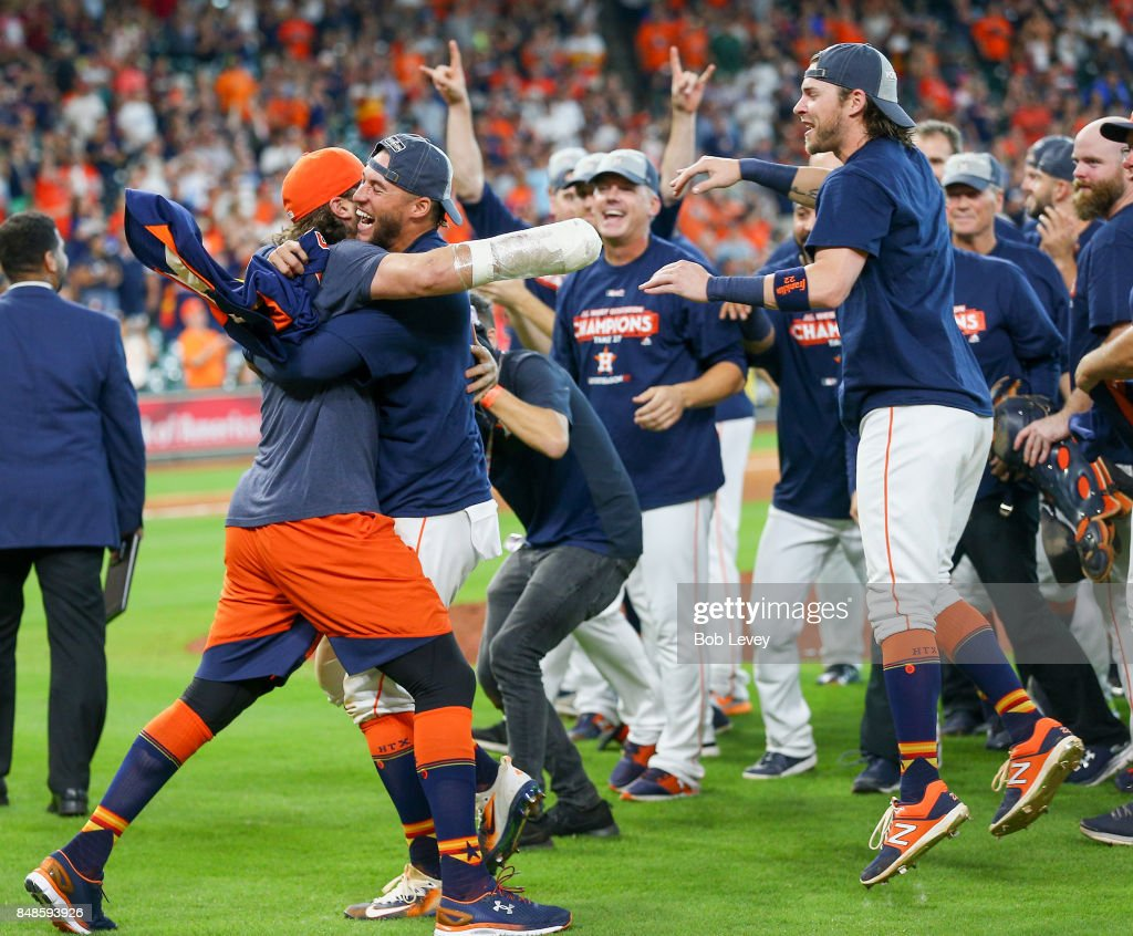 Jake Marisnick #6 (L) celebrates with George Springer #4 and Josh Reddick #22 after winning the American League West division at Minute Maid Park on September 17, 2017 in Houston, Texas.