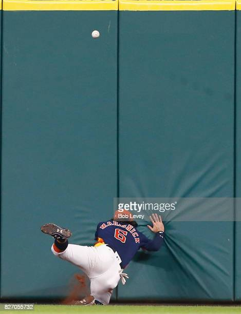 Jake Marisnick of the Houston Astros hits the wall as he attempts a play on a line drive hit by Justin Smoak of the Toronto Blue Jays in the seventh...