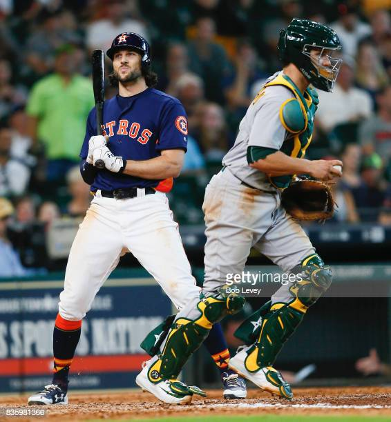Jake Marisnick of the Houston Astros is caught looking a called strike three to end the game as Dustin Garneau of the Oakland Athletics walks away at...