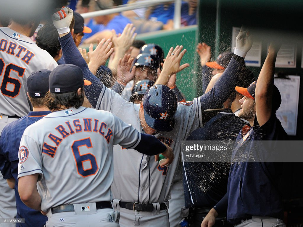 Jake Marisnick #6 of the Houston Astros tosses water on George Springer #4 after Springer hit a grand slam in the first inning against the Kansas City Royals at Kauffman Stadium on June 24, 2016 in Kansas City, Missouri.