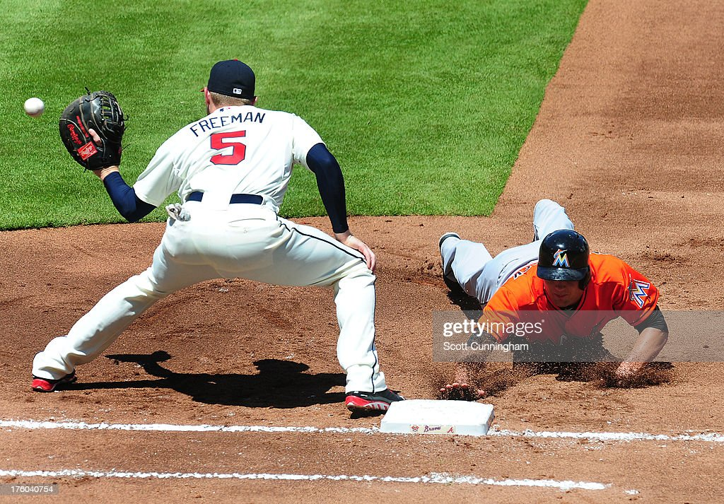 Jake Marisnick #23 of the Miami Marlins dives back to first base against <a gi-track='captionPersonalityLinkClicked' href=/galleries/search?phrase=Freddie+Freeman&family=editorial&specificpeople=5743987 ng-click='$event.stopPropagation()'>Freddie Freeman</a> #5 of the Atlanta Braves at Turner Field on August 11, 2013 in Atlanta, Georgia.