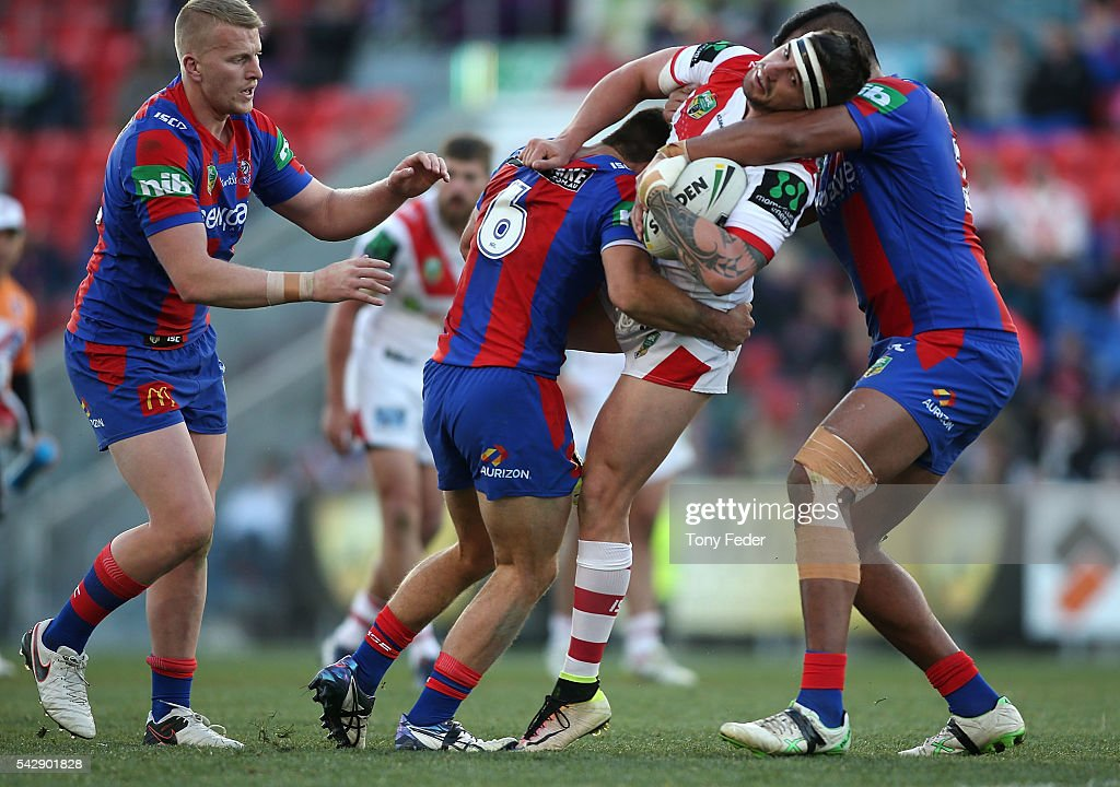 Jake Marketo of the Dragons is tackled by the Knights defence during the round 16 NRL match between the Newcastle Knights and the St George Illawarra Dragons at Hunter Stadium on June 25, 2016 in Newcastle, Australia.