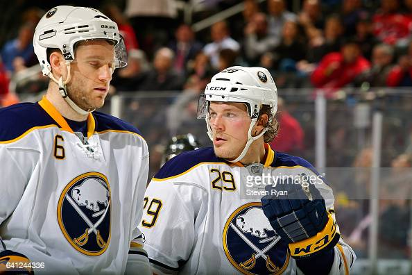 Jake McCabe of the Buffalo Sabres speaks with teammate Cody Franson against the New Jersey Devils during the second period at Prudential Center on...