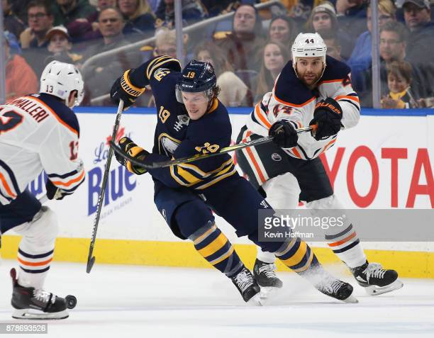 Jake McCabe of the Buffalo Sabres tries to skate between Michael Cammalleri of the Edmonton Oilers and Zack Kassian during the second period at the...