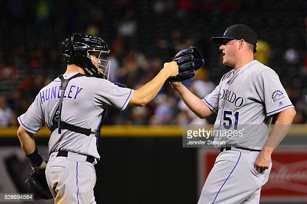 Jake McGee of the Colorado Rockies is congrateulated by Nick Hundley after closing out the game against the Arizona Diamondbacks at Chase Field on...