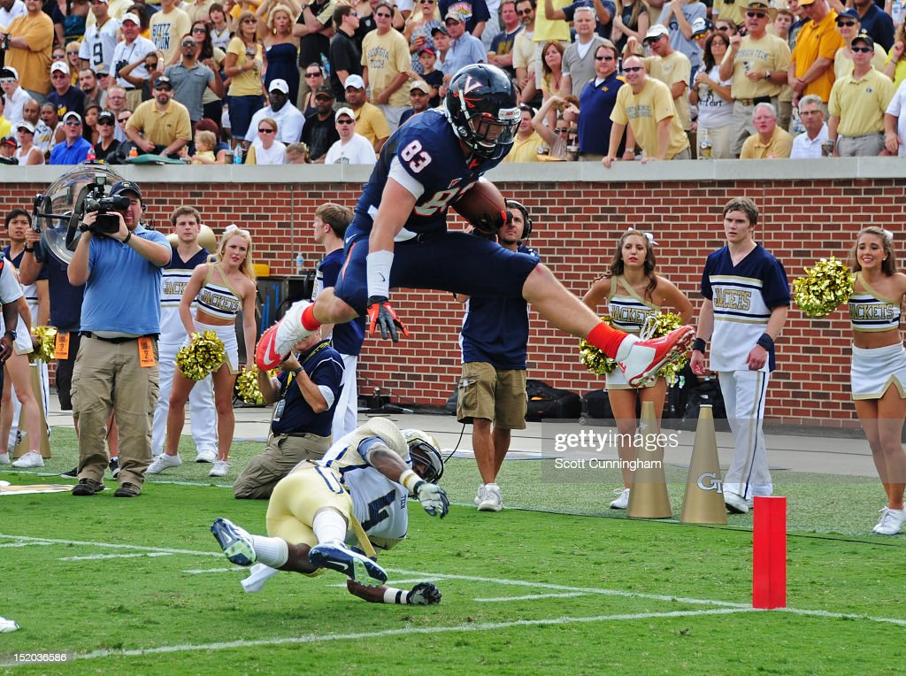 Jake McGee #83 of the Virginia Cavaliers leaps over Jamal Golden #4 for a touchdown against the Georgia Tech Yellow Jackets at Bobby Dodd Stadium on September 15, 2012 in Atlanta, Georgia.