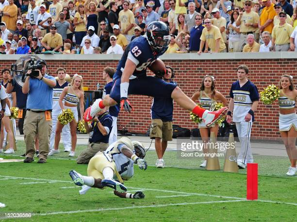 Jake McGee of the Virginia Cavaliers leaps over Jamal Golden for a touchdown against the Georgia Tech Yellow Jackets at Bobby Dodd Stadium on...