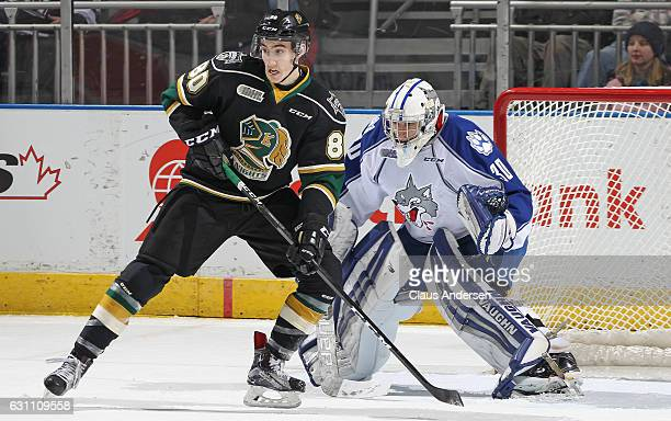 Jake McGrath of the Sudbury Wolves tries to look past a screening Alex Formenton of the London Knights during an OHL game at Budweiser Gardens on...