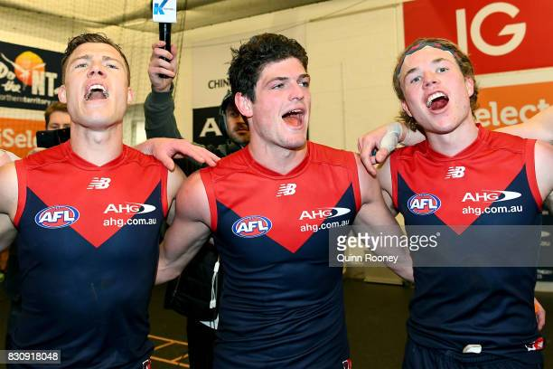 Jake Melksham Angus Brayshaw and Jayden Hunt of the Demons sing the song in the rooms after winning the round 21 AFL match between the Melbourne...