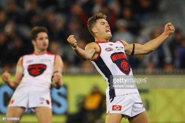 Jake Melksham of the Demons celebrates a goal over Liam Jones of the Blues in the dying stages during the round 16 AFL match between the Carlton...