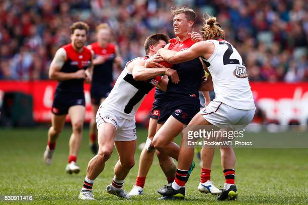 Jake Melksham of the Demons is gang tackled by Josh Bruce of the Saints and Jack Sinclair of the Saints during the round 21 AFL match between the...