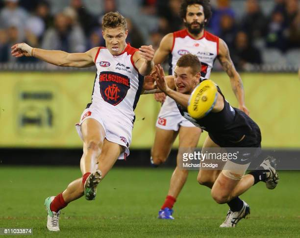 Jake Melksham of the Demons kicks the ball for the match winning goal against Liam Jones of the Blues in the dying stages during the round 16 AFL...