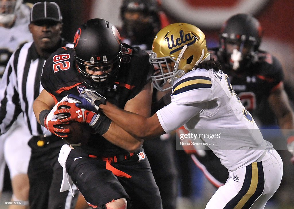Jake Murphy #82 of Utah is arm tackled by Randall Goforth #3 of UCLA in the first quarter at Rice- Eccles Stadium October 3, 2013 in Salt Lake City, Utah.