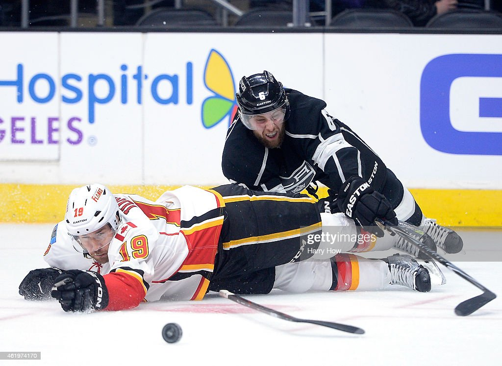 Jake Muzzin #6 of the Los Angeles Kings and David Jones #19 of the Calgary Flames fall to the ice while chasing the puck during the first period at Staples Center on January 19, 2015 in Los Angeles, California.
