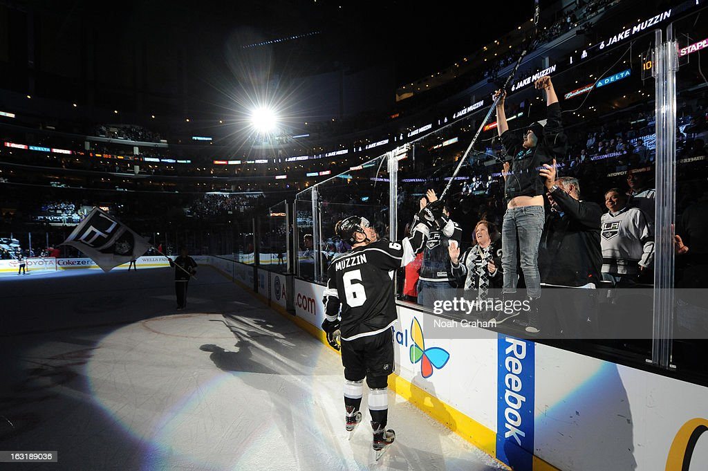 Jake Muzzin #6 of the Los Angeles Kings hands his stick to a fan after a game against the St. Louis Blues at Staples Center on March 5, 2013 in Los Angeles, California.