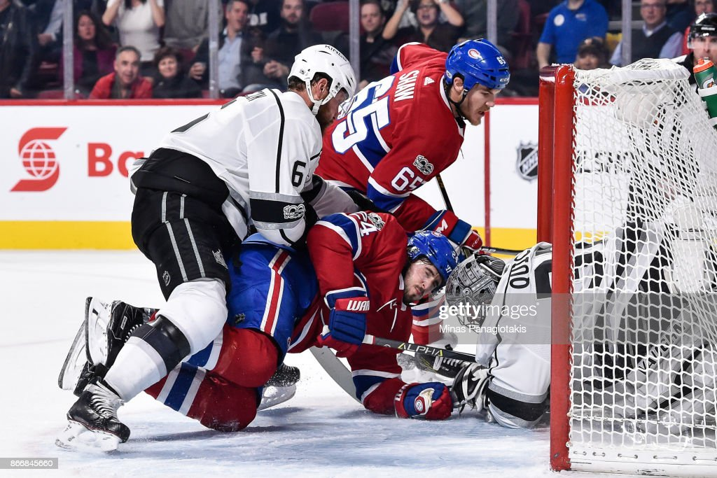 Jake Muzzin #6 of the Los Angeles Kings pushes Phillip Danault #24 of the Montreal Canadiens into goaltender Jonathan Quick #32 during the NHL game at the Bell Centre on October 26, 2017 in Montreal, Quebec, Canada.
