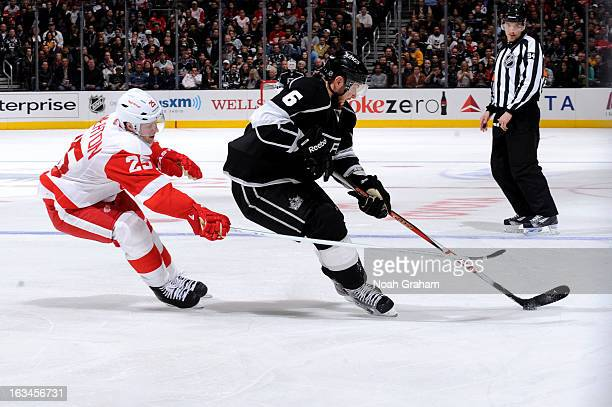 Jake Muzzin of the Los Angeles Kings skates with the puck against Cory Emmerton of the Detroit Red Wings at Staples Center on February 27 2013 in Los...