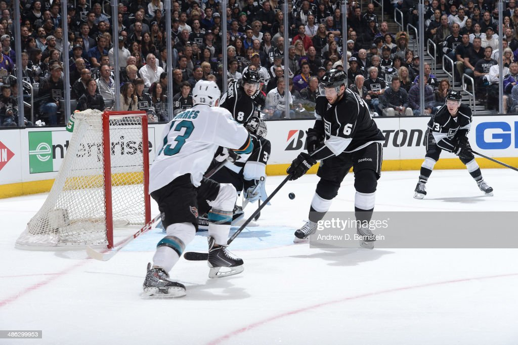 Jake Muzzin of the Los Angeles Kings takes a shot on goal against Raffi Torres of the San Jose Sharks in Game Three of the First Round of the 2014...